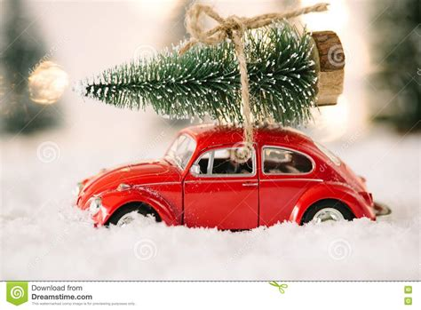 red car toy carrying christmas tree stock image