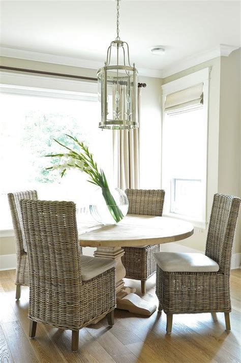 salvaged wood dining table with white wicker dining chairs
