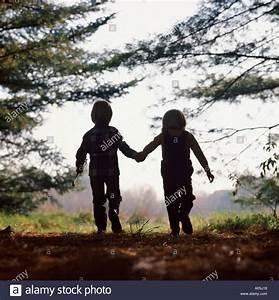 Hand In Hand Gehen : partielle silhouette eines paares der kinder hand in hand gehen am rande des waldes stockfoto ~ Orissabook.com Haus und Dekorationen