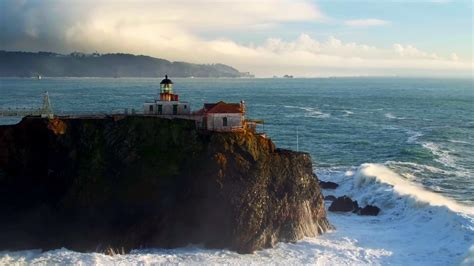 Aerial view of lighthouse on cliff overlooking giant ocean ...