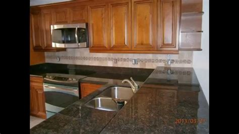 caramel glazed kitchen cabinets with black granite west