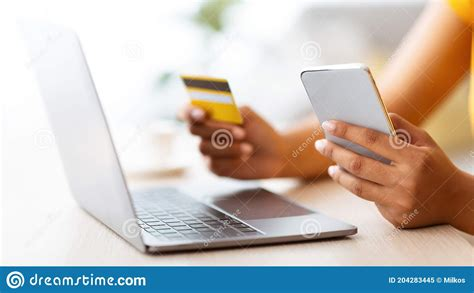 Paying bills using a debit card is just one more task people can handle by phone. Black Lady Using Smartphone And Credit Card Sitting At Desk Stock Image - Image of discount ...