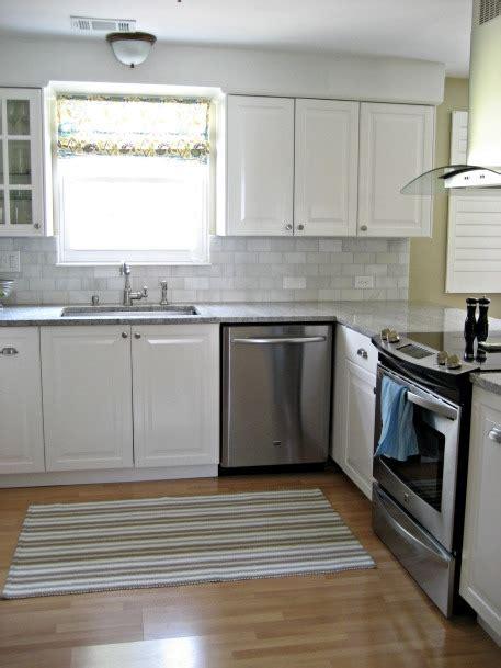 White kitchen with gray subway tile, white carrara marble
