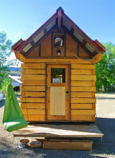 man builds log cabin tiny house hinged overhangs