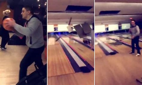 man attempting  throw bowling ball hits ceiling brings