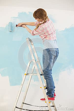 woman  ladder painting wall  paint roller stock