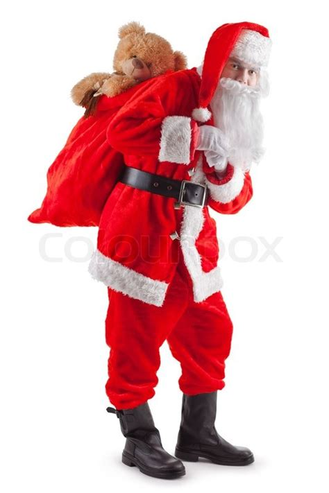 standing santa claus with a bag of gifts stock photo