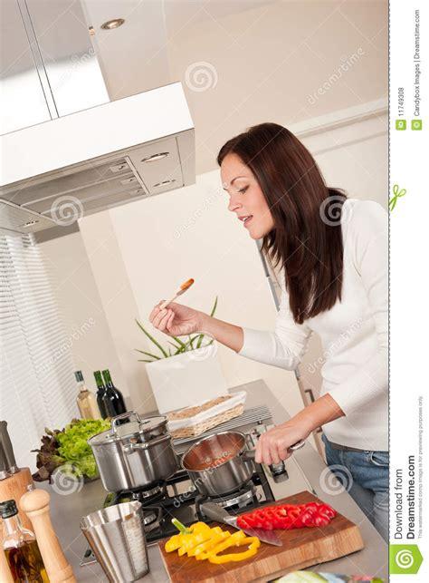 femme cuisine femme heureuse faisant cuire la sauce tomate dans la