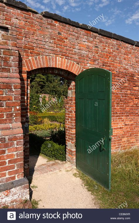 open brick wall open green door in red brick wall leading to walled
