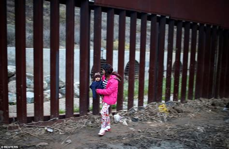 migrants attempt early morning clamber  mexico border