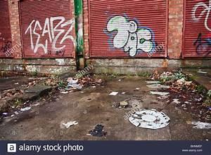 Graffiti on garage doors in urban street littered with ...