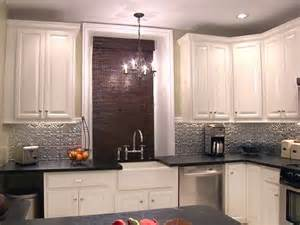 silver backsplash black countertops white cabinets