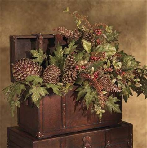 holiday decorating with greenery pine cones in wooden trunks
