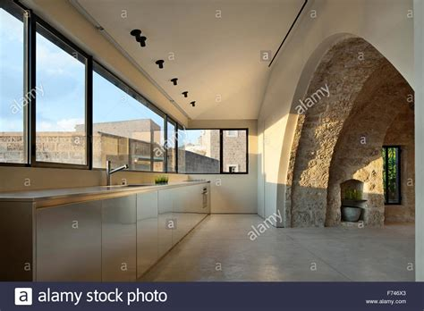exposed stone arch  minimalist kitchen  uncurtained