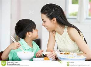 Chinese Mother And Son Sitting At Home Eating Stock Image