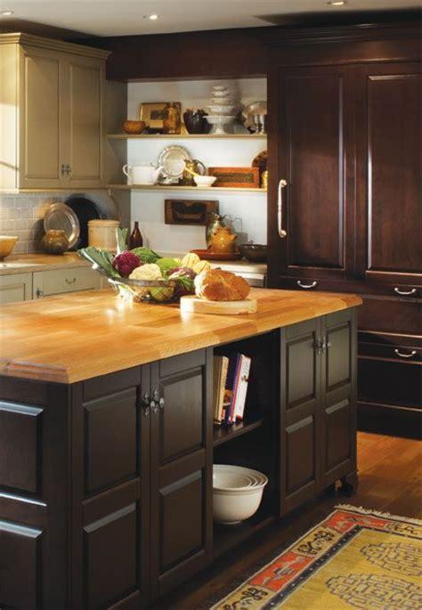 kitchen: butcher block countertop, dark cabinets, light