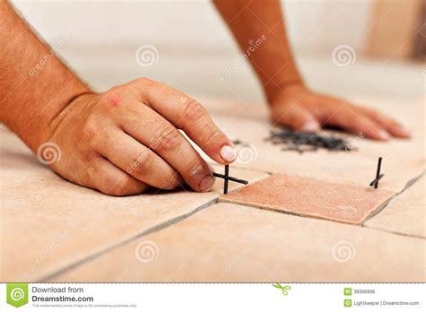 worker placing spacers between ceramic floor tiles