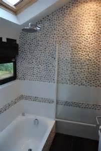 une salle de bain sous pente recouverte de galets