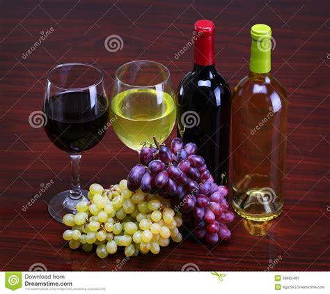 bicchieri di rosso bottiglie di rosso e bianco con l uva fresca