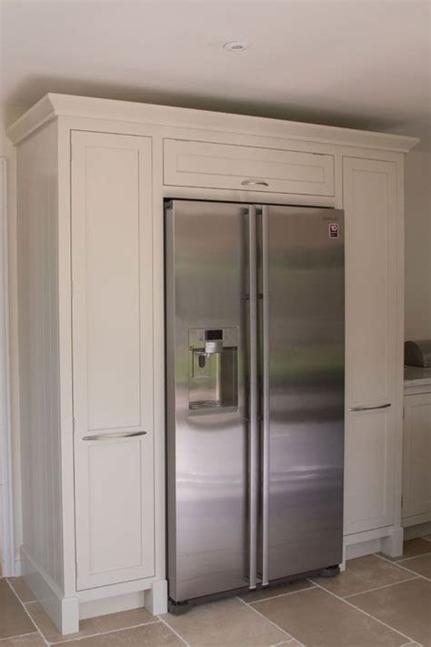 american fridge freezer surrounded  handmade cabinetry