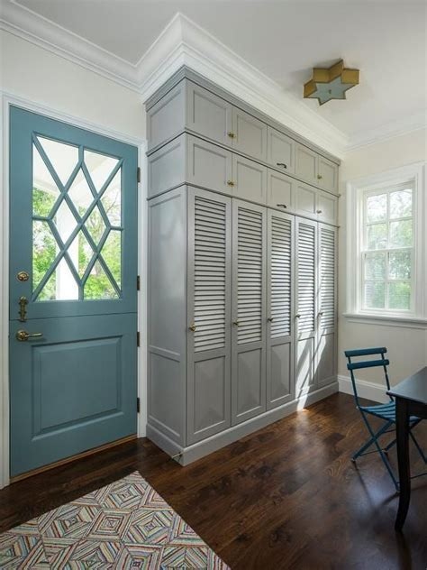 A turquoise blue door opens to a mudroom features built in