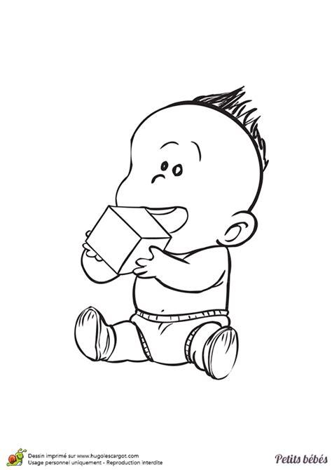 coloriage d un petit bébé qui joue avec un cube en bois