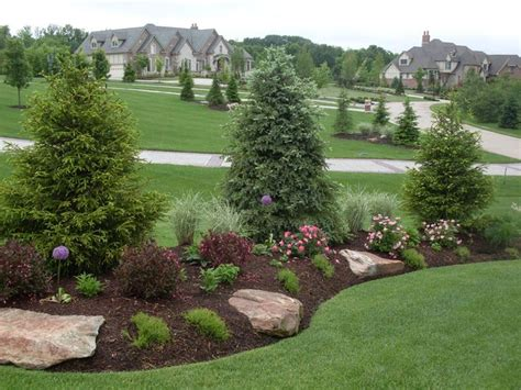berm landscaping ideas sweet this berm features evergreen screening boulder accents and pops of color achieved with