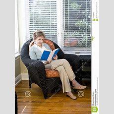 Senior Woman Sitting On Living Room Chair Reading Stock