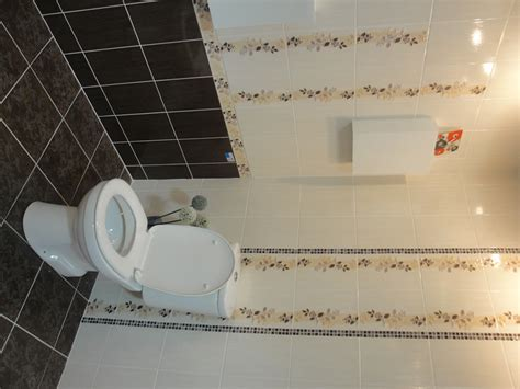 Tiling A Bathroom Floor Around A Toilet by Using A Mosaic Tile As A Vertical Border Around A Toilet