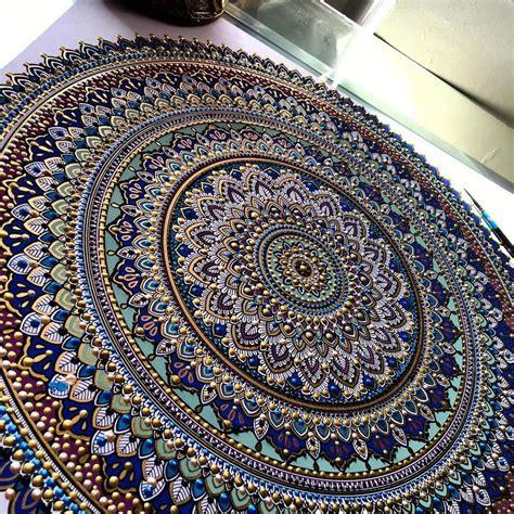 artist creates intricate mandala designs gilded  gold