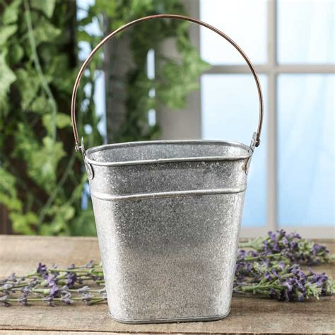 Slotted galvanized metal wall bucket features a galvanized metal construction of a halved olive bucket shape that is designed to sit against the wall. Small Galvanized Tin Wall Pocket - Baskets, Buckets, & Boxes - Home Decor