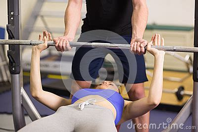 Trainer Helping Woman To Lift The Barbell Bench Press In
