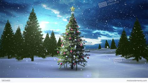 snow falling christmas tree in snowy landscape stock