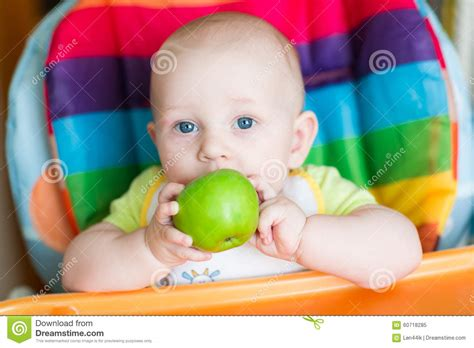 Adorable Baby Eating Apple In High Chair Stock Photo