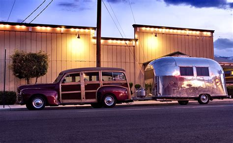 1950 s woody station wagon towing an airstream trailor parked in bishop california usa martyn