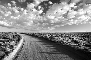 White And Black : grayscale photo of empty road between grass field under cloudy sky free stock photo ~ Medecine-chirurgie-esthetiques.com Avis de Voitures