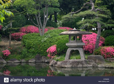 Typical Stone Lantern With Bright Pink Plants In A