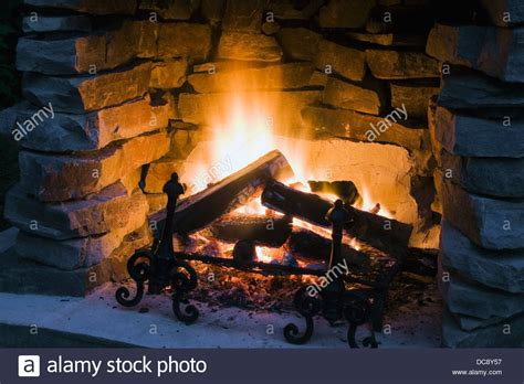 Burning Logs In A Stone Fireplace Outdoors At Dusk Quebec