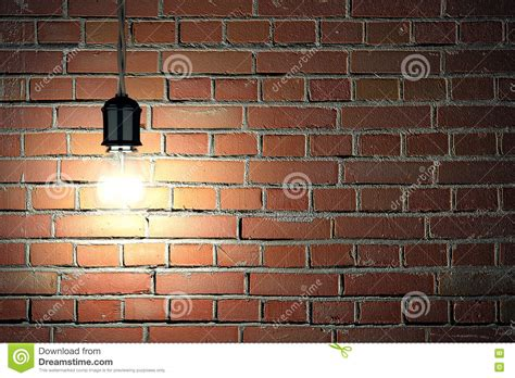 light bulb on dark brick wall background stock image