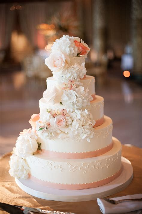 White Wedding Cake With Peach Ribbon And Cascading Flowers