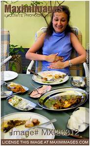 Photo Of Woman Overeaten At A Restaurant Holding Her