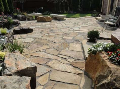 backyard patio with boulders and flagstone pavers