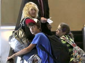 A slightly frazzled looking Laura Dern leads her son ...