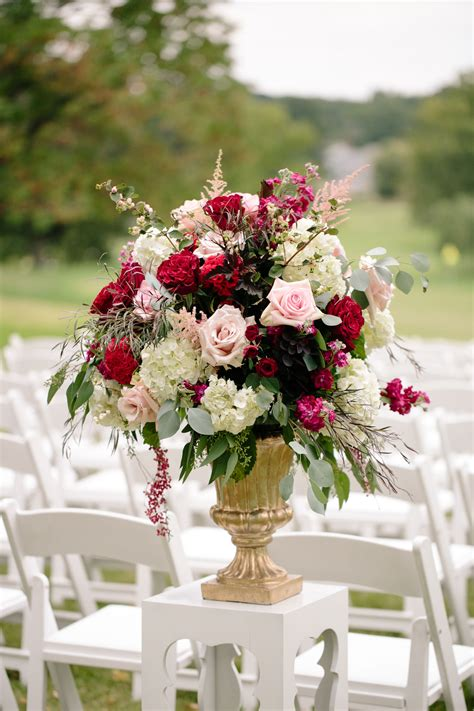 gold pedestal ceremony arrangement  pink roses  red