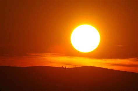 matahari pillow a big sun setting photograph by jeff swan