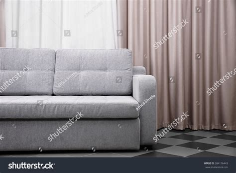 grey sofa against curtains in the room stock photo