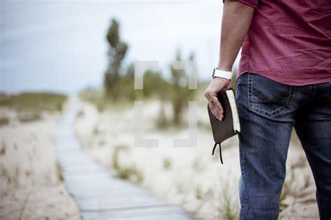 man holding  bible walking   boardwalk photo