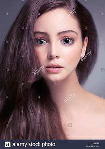 Cute young woman face with big gray eyes and long brown ...