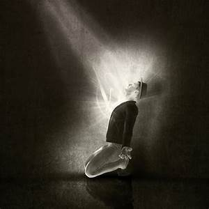 Man on his knees with a ray of light Photo | Free Download