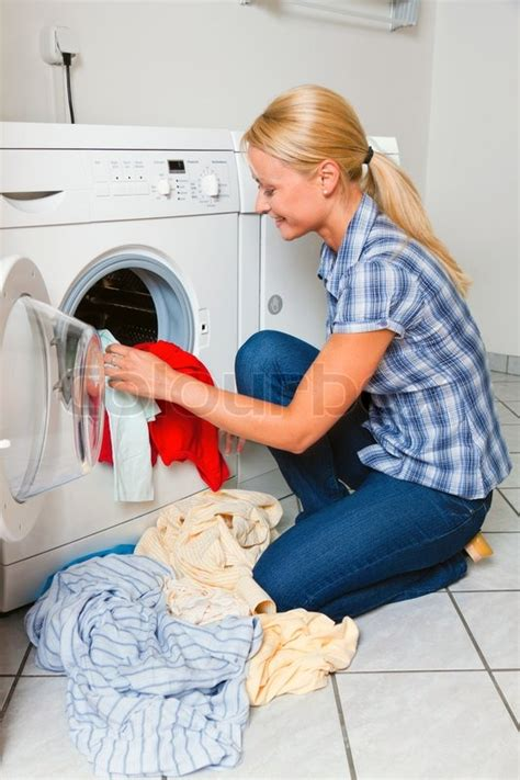 A Young Housewife With Washing Machine And Clothes